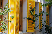 Old yellow wooden windows shutters of mediterranean house