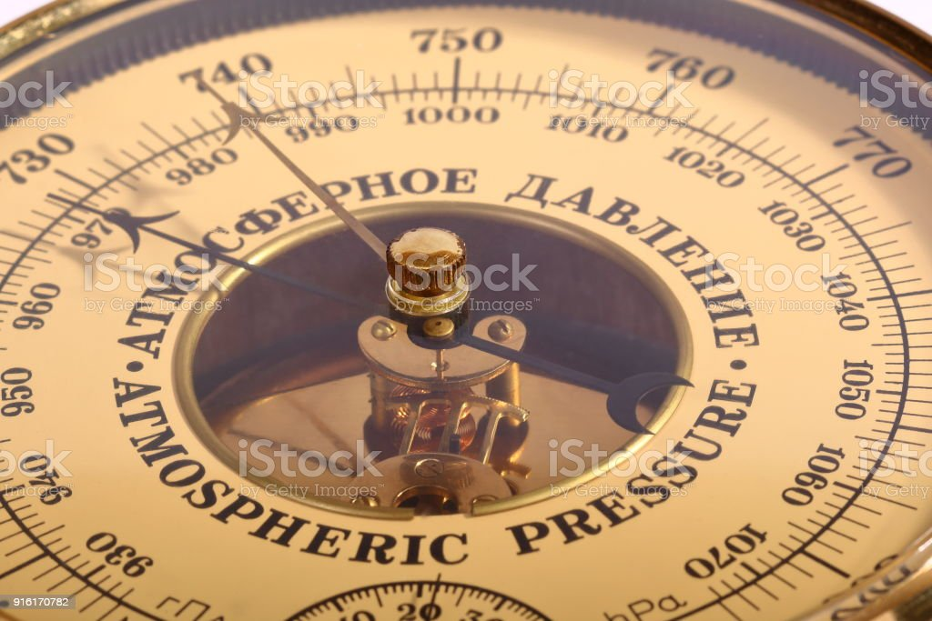 Old yellow-brown aneroid barometer in wooden body close-up stock photo