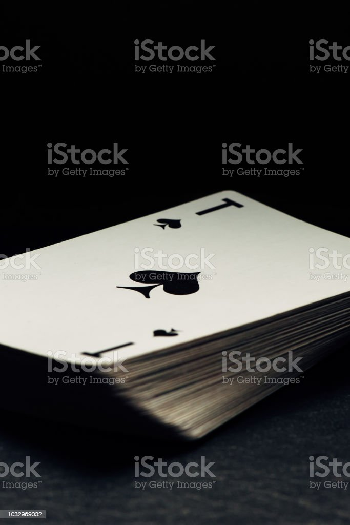 Old yellowed deck of cards on black background. Ace of spades lies on top. – zdjęcie