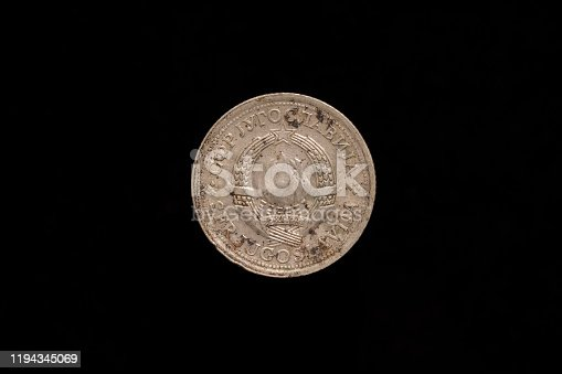Socialist Federal Republic of Yugoslavia old stained 1 Dinar coin from 1976, obverse showing the state emblem of Yugoslavia. Isolated on black background