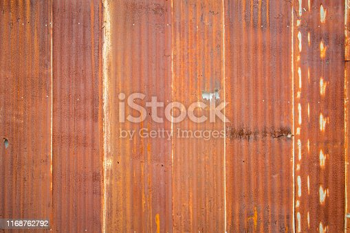 638964834istockphoto Old Zinc rust texture background, close up to pattern texture vertical zinc sheet. Abstract  Image of Rusty corrugated metal vintage background. Wall steel older dirty grunge surface fence house. 1168762792