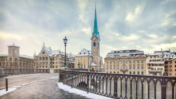 Old Zurich town in winter, view on lake Winter landscape of Zurich with lake with bridge on foreground, Switzerland fraumunster stock pictures, royalty-free photos & images