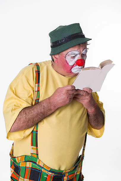 Old-aged Clown with book stock photo