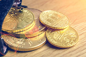 Gold and silver coins in close up isolated on light gray background.