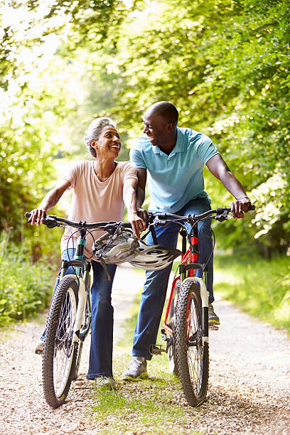 Older African-American could riding bicycles on narrow lane stock photo