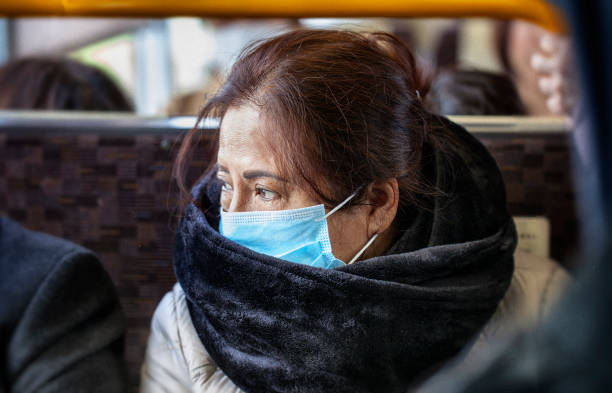 Older Asian woman wearing black fur scarf and surgical pollution mask sitting on a bus Older Asian woman wearing black fur scarf and surgical pollution mask sitting on a bus environmental damage stock pictures, royalty-free photos & images