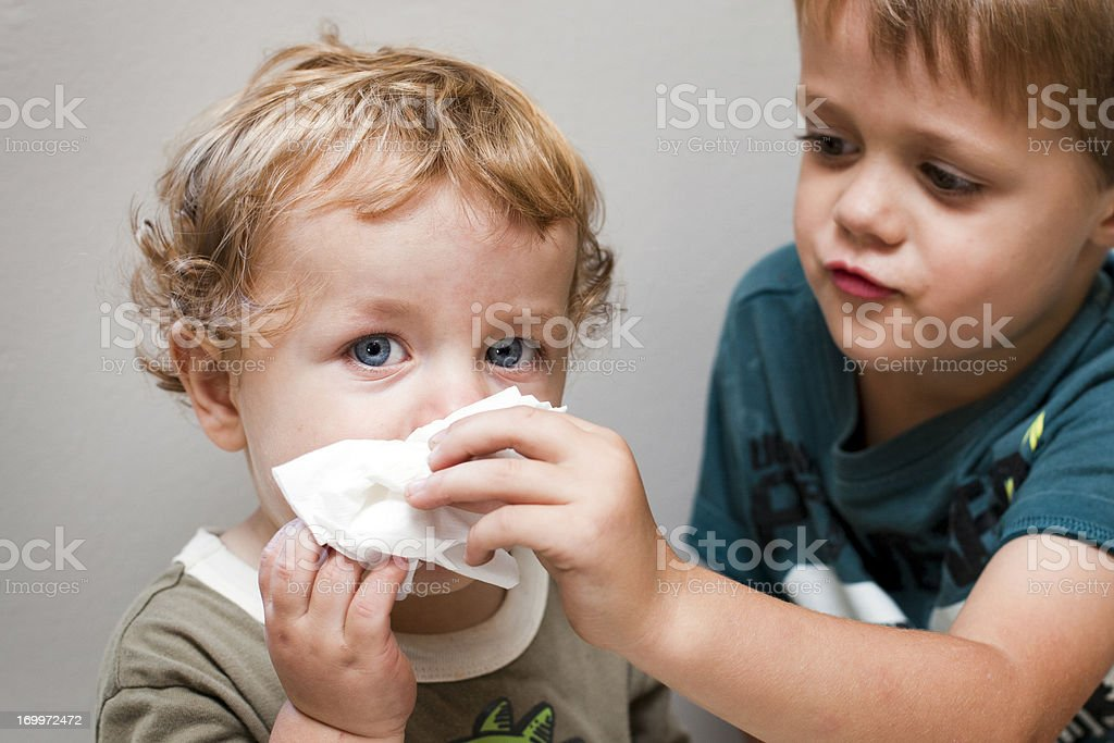 Older boy helping a younger boy blow his nose stock photo