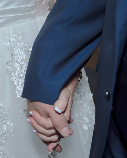 Older Bride and Groom holding hands stock photo