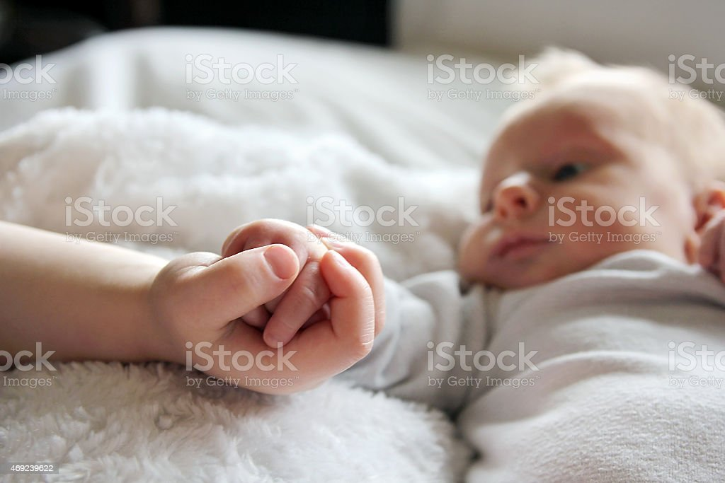 Older brother holding baby boy's little hand stock photo