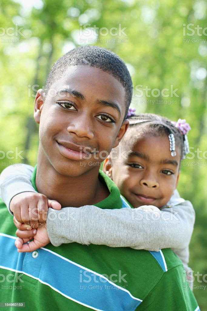 Older brother holding sister on his back for a photo stock photo