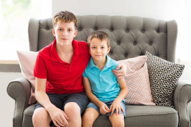 Older brother on the sofa hugging younger brother Older brother on the sofa hugging younger brother. Family portrait brother stock pictures, royalty-free photos & images