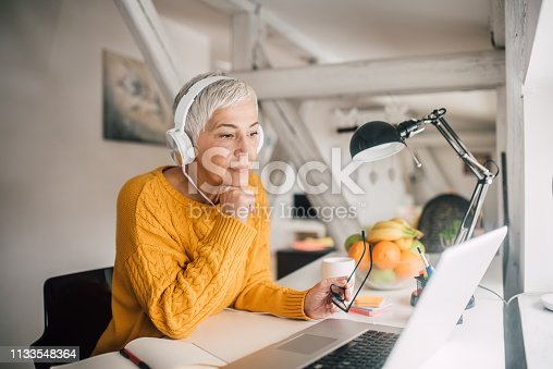 Business woman wearing headphones at home office
