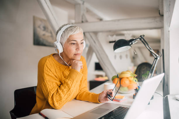 Older business woman with headphones Business woman wearing headphones at home office headphones stock pictures, royalty-free photos & images
