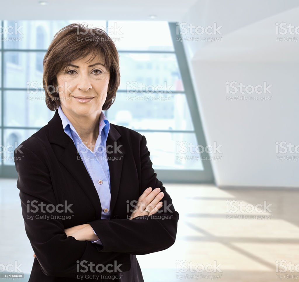 Older businesswoman standing with arms crossed in empty room royalty-free stock photo
