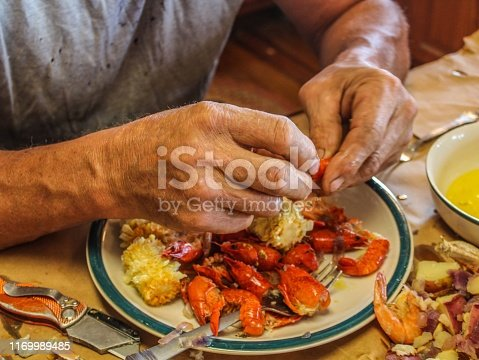 Older Caucasian man with gray moustache and unusually large hands picking seafood with a utility knife at a Cajun seafood boil including crabs, crawfish shrimp potatoes and corn served traditionally on brown paper