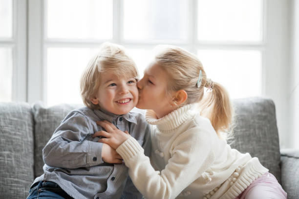 older child sister embracing kissing little younger brother at home - kids kiss embarrassed foto e immagini stock