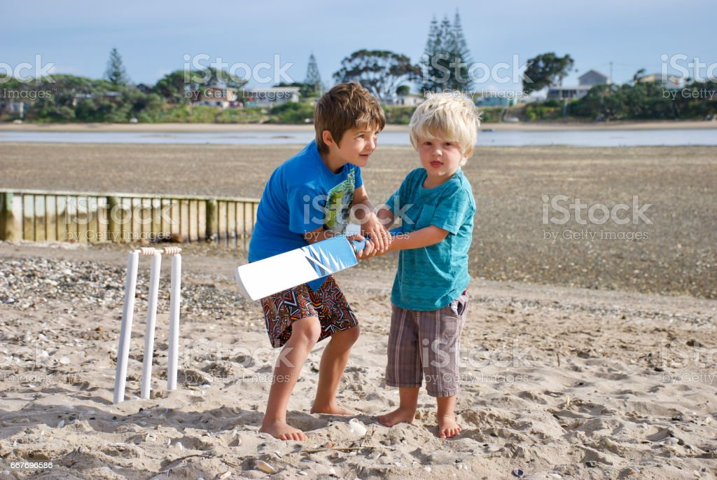 Older Child teaching Younger Child Cricket stock photo