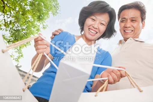Older Chinese couple smiling and carrying shopping bags