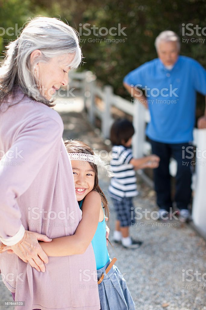 Older couple and grandchildren walking outdoors royalty-free stock photo