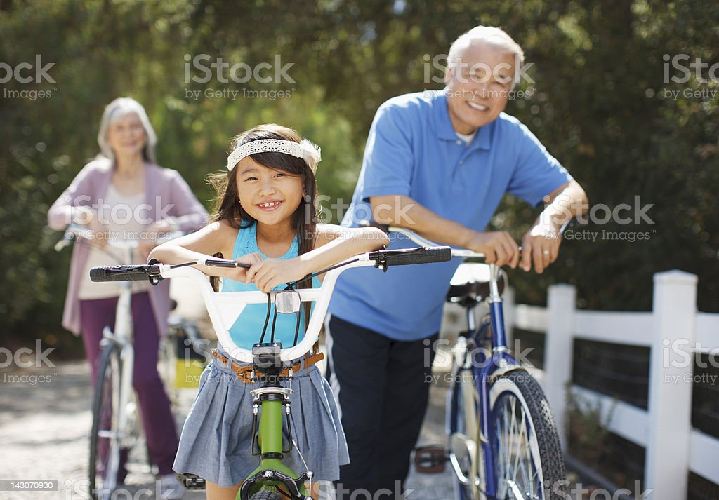 Older couple and granddaughter riding bicycles outdoors stock photo