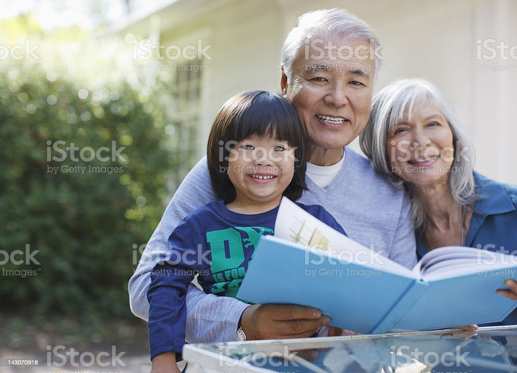 Older couple and grandson reading together stock photo