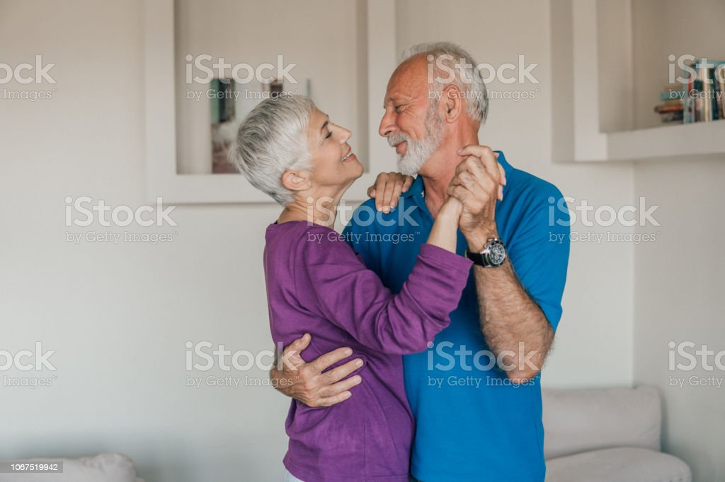 Senior couple in love dancing at home