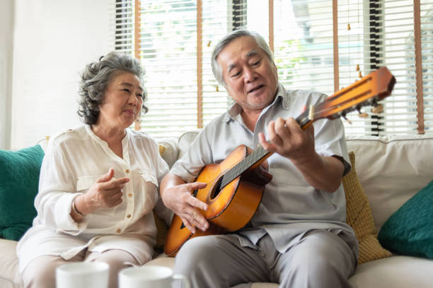 Older Couple enjoying with singing and guitar. Happy Retirement Older Couple enjoying with singing and guitar together. Having fun. 60 64 years stock pictures, royalty-free photos & images