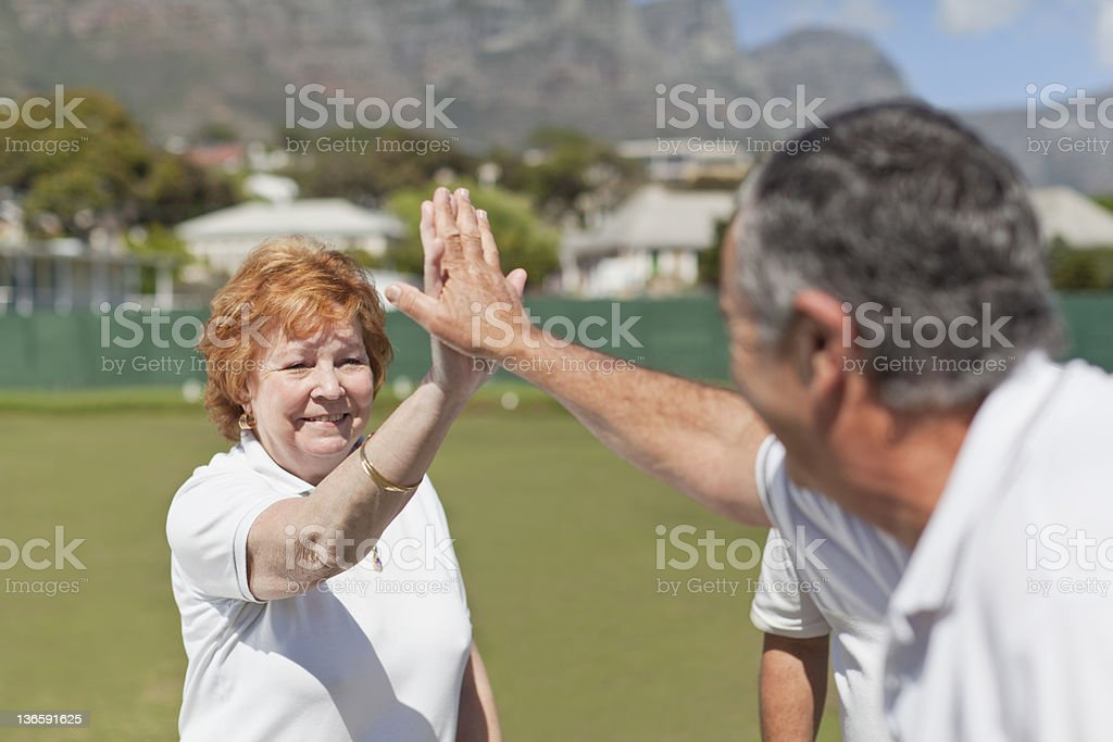 Older couple high fiving outdoors stock photo