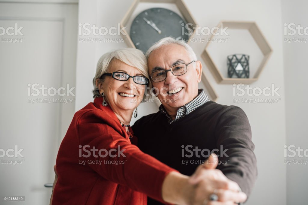Mature couple holding hands and dancing all over their home