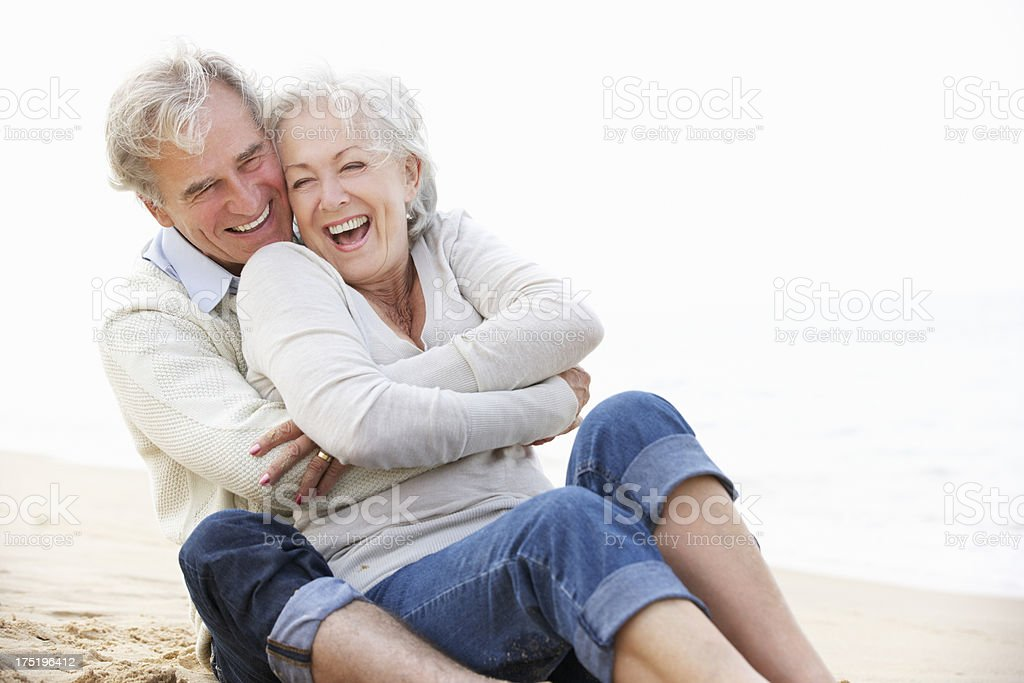 Older couple in white tops and jeans sitting on beach stock photo