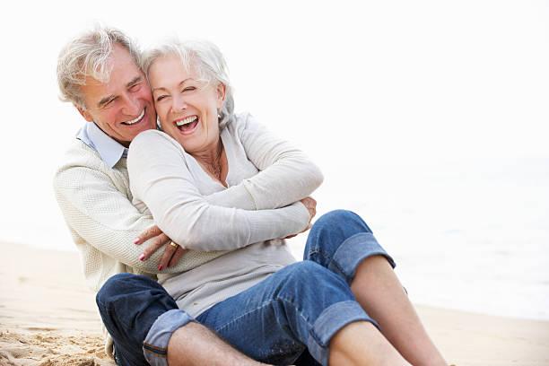 senior par sentado en la playa junto - pareja mayor fotografías e imágenes de stock
