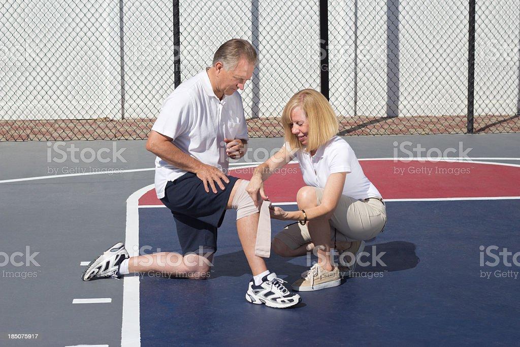 Older couple on basketball court applying tensor bandage to knee stock photo
