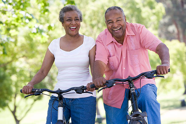 Older couple on bike ride in park stock photo