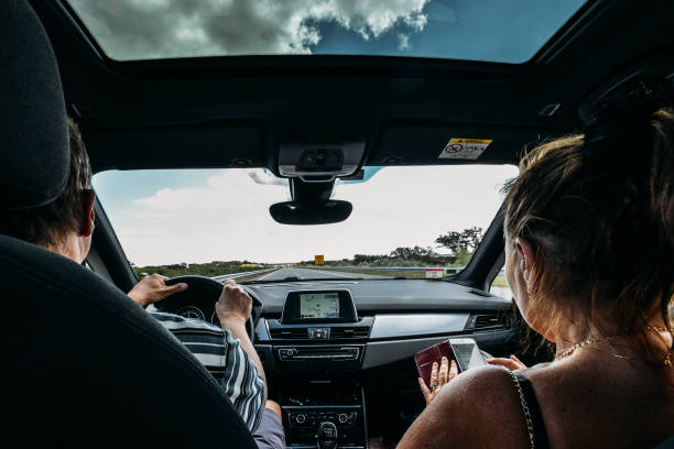 Older couple on front seat of car. Road trip concept. Woman uses a smartphone to pass the time while man drives stock photo