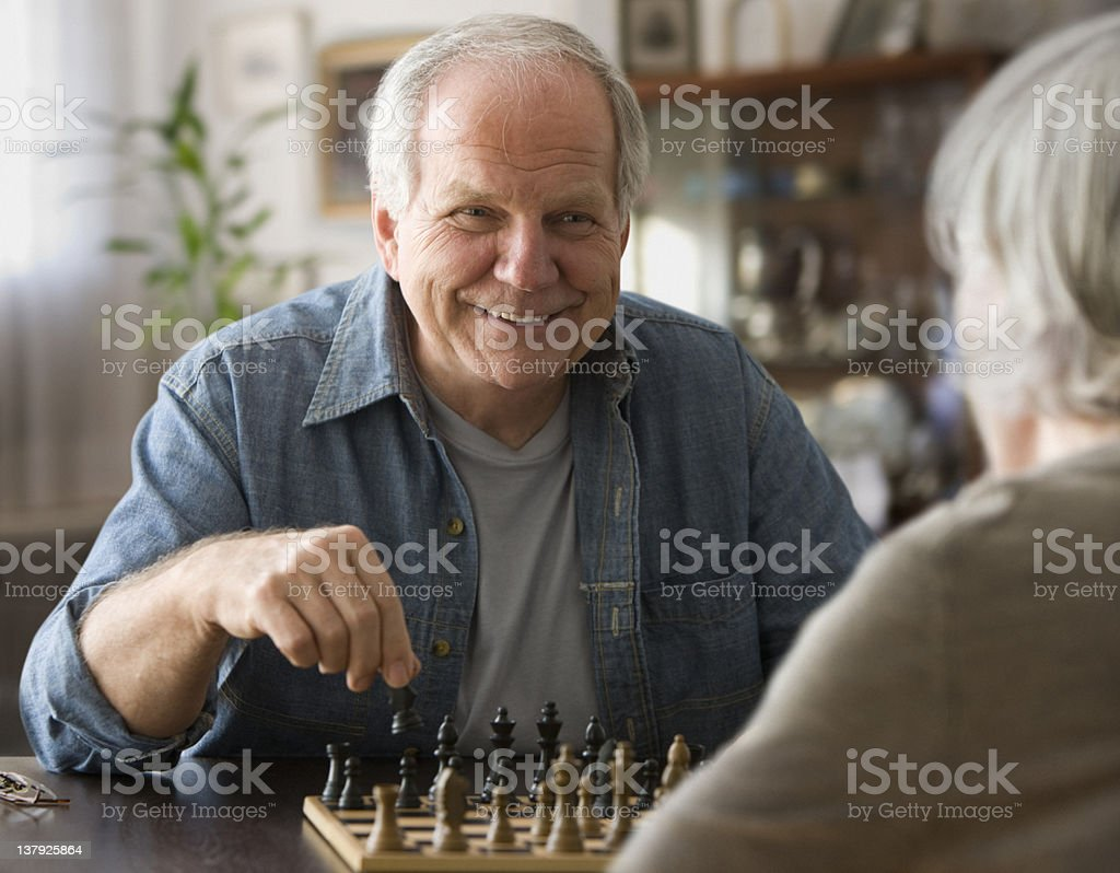 Older couple playing chess stock photo