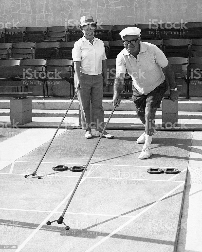 Older couple playing shuffleboard royalty-free stock photo