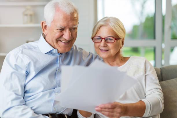 Älteres Ehepaar liest Papiere gemeinsam auf Sofa – Foto