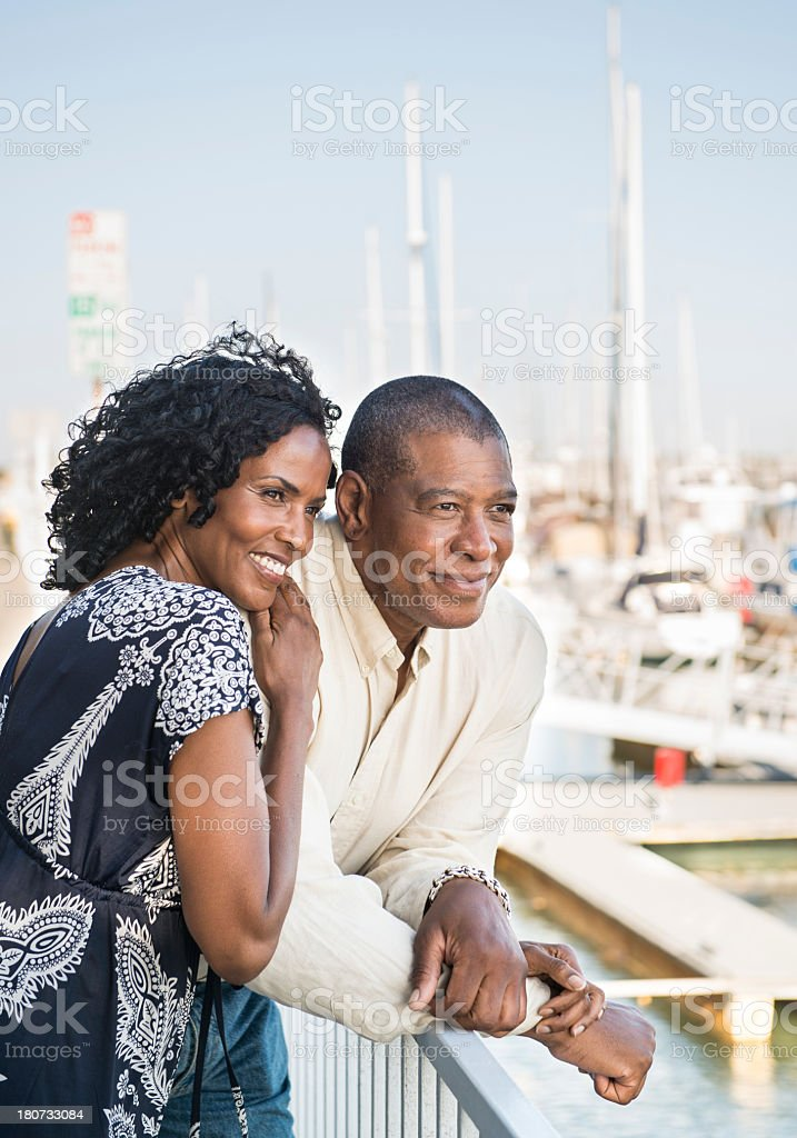 Older couple smiling at harbor stock photo
