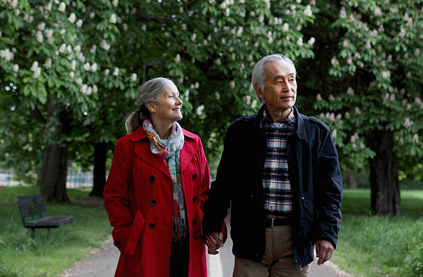 Older couple walking in park  65 69 years stock pictures, royalty-free photos & images