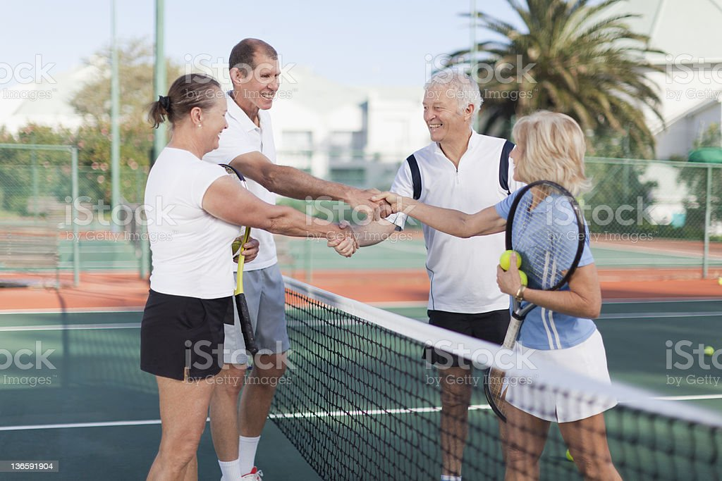 Older couples shaking hands at tennis stock photo