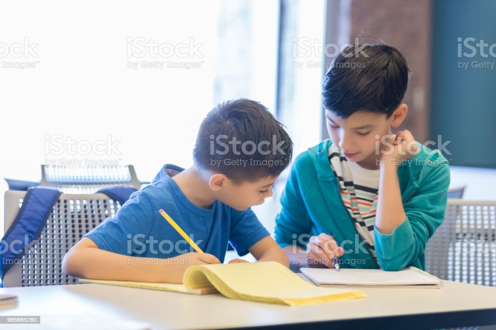 Confident older elementary school student helps a younger student...