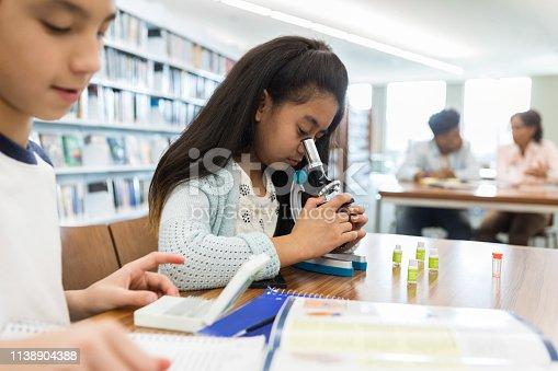 istock Older elementary schoolgirl uses microscope 1138904388