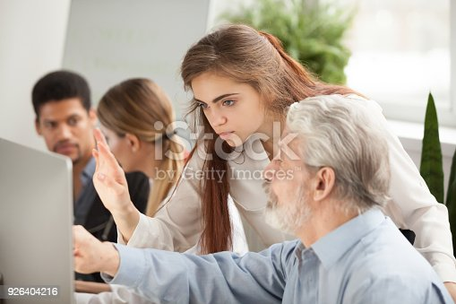 926404274 istock photo Older employee asking young manager question about online computer task 926404216