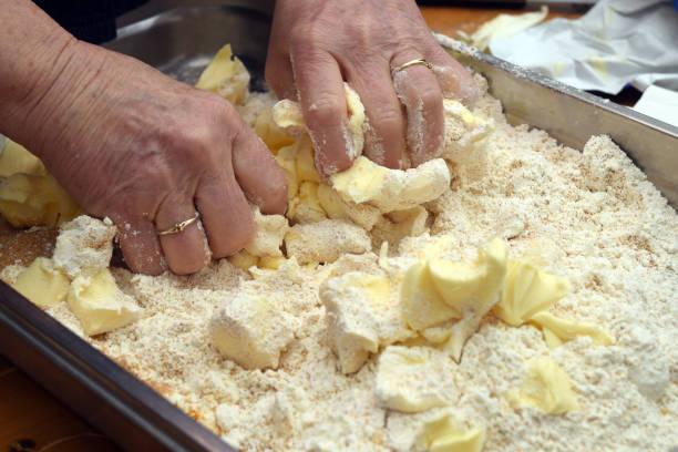 ältere weibliche hände sind einen teig aus butter und mehl zum backen einen kuchen, textfreiraum kneten. - ring anleitung stock-fotos und bilder