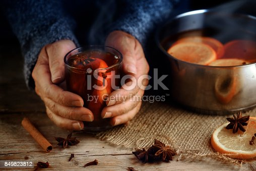 istock Older female hands holding a glass mug with hot mulled wine next to the steaming cooking pot,  Christmas ingredients, orange slices, cinnamon sticks, star anise and cloves, a warming home scene on a rustic wooden table 849823812