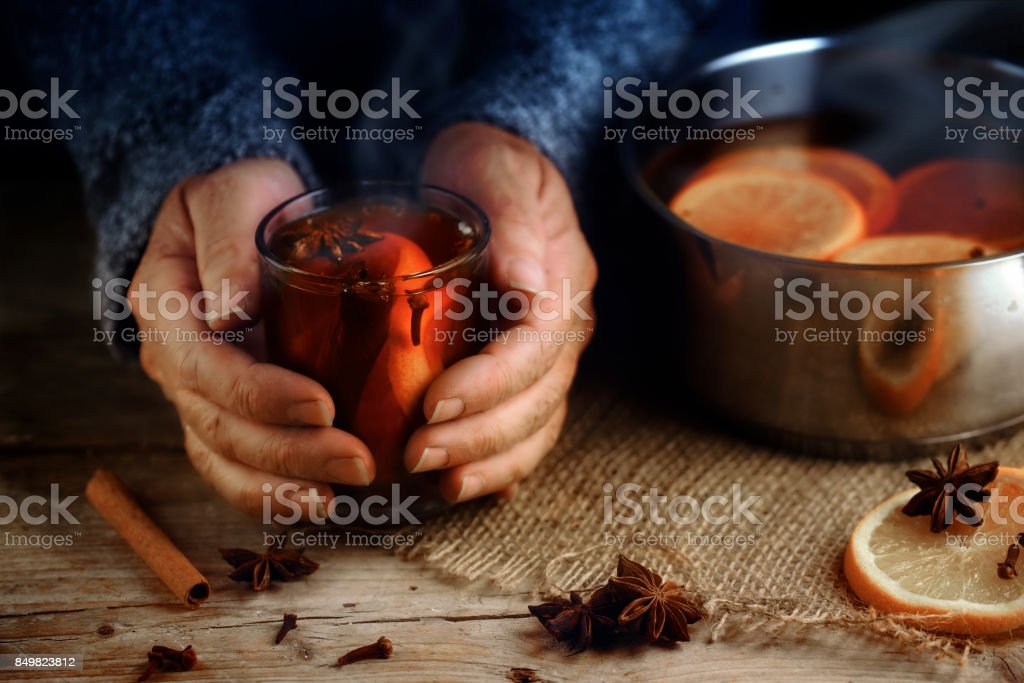 Older female hands holding a glass mug with hot mulled wine next to the steaming cooking pot,  Christmas ingredients, orange slices, cinnamon sticks, star anise and cloves, a warming home scene on a rustic wooden table stock photo