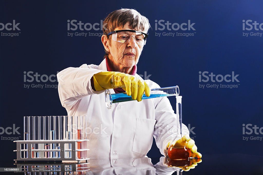 Older female scientist concentrates on mixing chemicals in lab stock photo