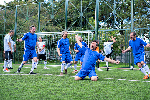 Older footballers celebrating a goal scored by the rival team
