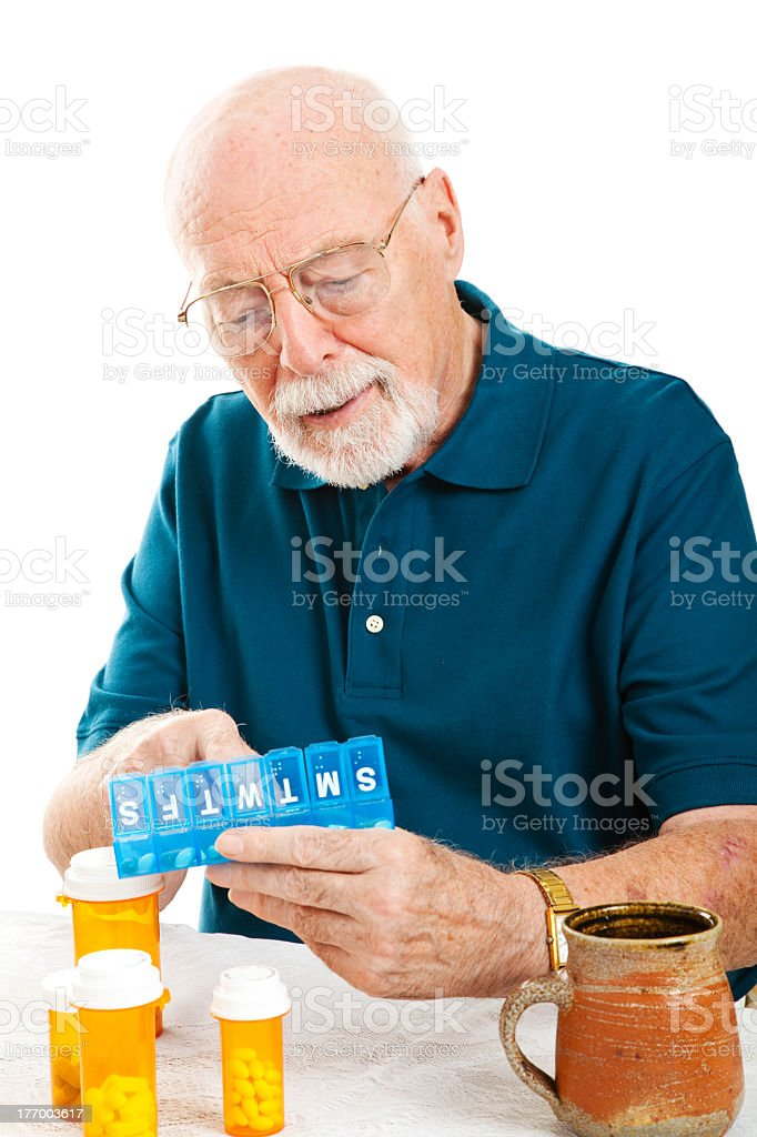Older gentleman sorting his weekly pills stock photo