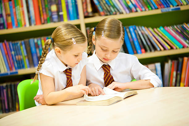 Older girl helping this younger pupil to read stock photo